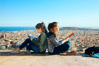 Image of two students in Spain enjoying the sun and reading